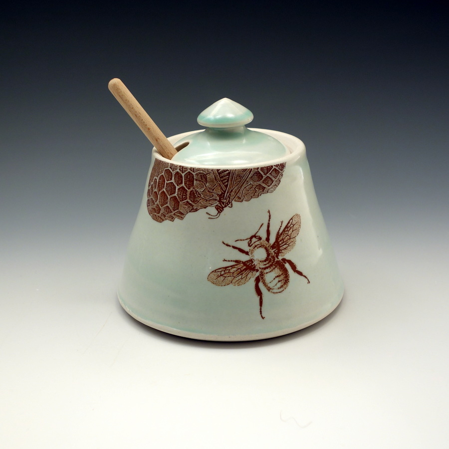 Celadon glazed porcelain honey pot with bees buzzing and honey comb